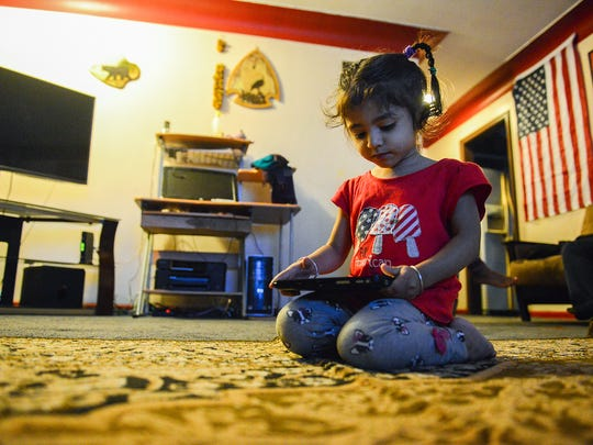 Bhim Dahal's two-year-old daughter Swara plays a game on a tablet at their home. She was born in Lansing after her father, grandparents and great-grandmother, all Nepali Hindus,  came to America as refugees in 2010.