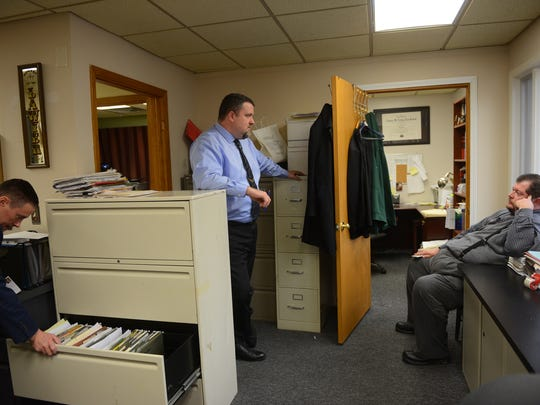 Attorney Stephen Cornish, left, looks for a file as