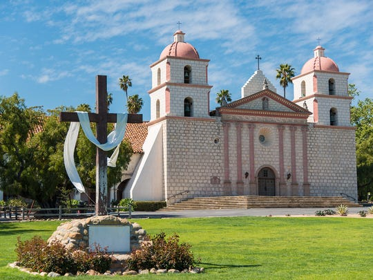 Mission Santa Barbara in Santa Barbara, California with a cross and a sky blue background.