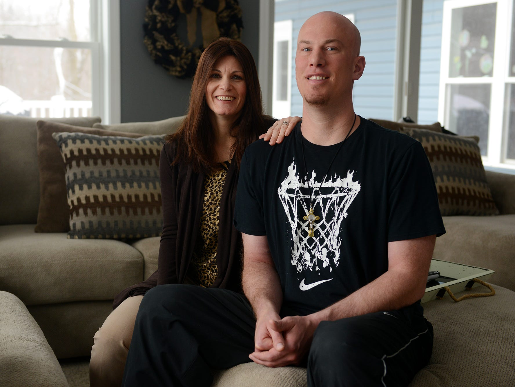 Williamston head basketball coach Jason Bauer and his wife Dawn pose for a portrait on Monday, March 13, 2017 at his home in Williamston. Around the same time last year, he was diagnosed with two brain tumors.