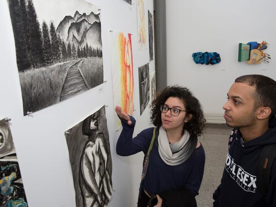The Visual Arts Student Exhibition, an annual showcase of the work of Middlesex County College students in art classes, kicked off with a reception. The exhibition will be on display in the Studio Theater Gallery on the Edison campus weekdays from 11 a.m. to 4 p.m. until April 17 (except April 14).  The exhibit includes drawing, painting, sculpture and mixed media. Here, Kristal Ruiz of Carteret shows off her painting to fellow artist Adrian Maldonado of  Perth Amboy.