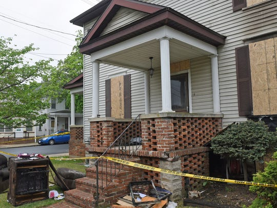 Caution tape still surrounds a house Monday at 589
