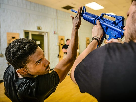 Emmanuel Williams, left, practices a long gun disarming technique with Wade Bowers during a krav maga class at The Trainers Studio Thursday May 18, 2017 in Lansing.