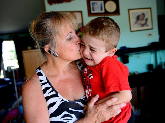 Leona Simon of Grand Ledge, picks up her grandson Carl Cole after he became upset during an August interview. Carl has a genetic condition that causes muscle weakness.