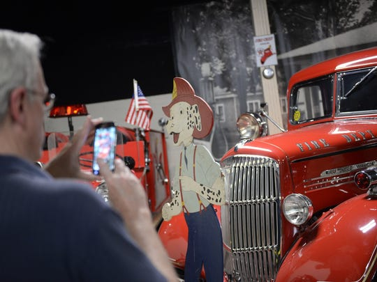 Mark Jensen takes a photo of the permanent first responders exhibit on Saturday at the R.E. Olds Transportation Museum in Lansing. The exhibit is a  display of cars, call boxes, uniforms, honor board with firefighters and police officers who have lost their lives on duty.