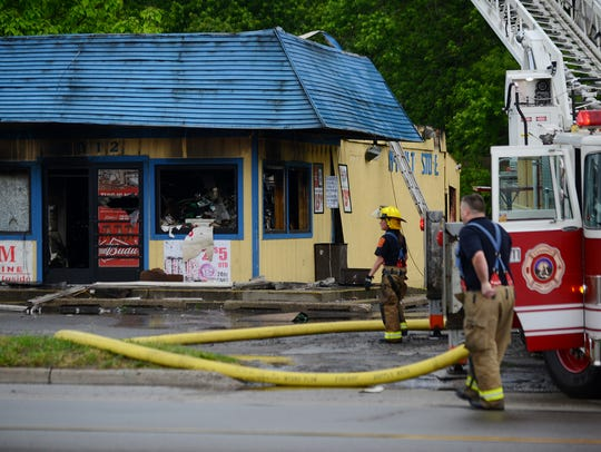 Crews work the scene of a fire at the M-9 Party Store
