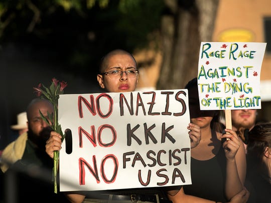Brenda Diaz-Castro, holds a sign during a candlelight vigil on Sunday, Aug. 13, 2017, in Harrisonburg, Va. The vigil was held for the victims of the violence in Charlottesville, Va., on Saturday. (Stephen Swofford/Daily News-Record via AP)