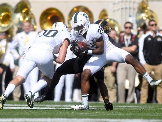 Michigan State's Josiah Scott intercepts a pass intended