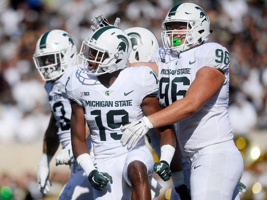 Michigan State's Josh Butler, left, celebrates his sack with teammate Jacub Panasiuk during the second quarter on Saturday, Sept. 9, 2017, at Spartan Stadium in East Lansing.