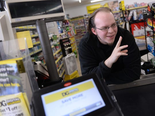 Lucas Holliday waves to a customer while posing for a portrait on Nov. 15, 2016, at the Dollar General, 5640 S. Martin Luther King Blvd. in Lansing. A video of Holliday singing behind the cash register went viral.
