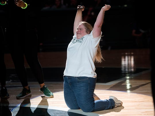 Michigan State women's baseball super fan Stephanie Russell celebrates after kissing the Spartans logo at center court during the annual Midnight Madness event on Friday, Oct. 20, 2017, at the Breslin Center in East Lansing.