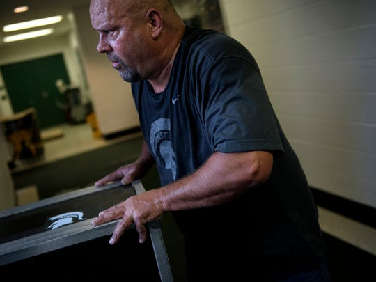 Glenn Edgett pushes a crate into the Michigan State football team's equipment semi trailer at the Duffy Daugherty Football Building on Thursday, Oct. 26, 2017, in East Lansing. Edgett will drive the equipment to Evanston for MSU's game against Northwestern. Edgett has been delivering the Spartans football equipment to away games for nine years.