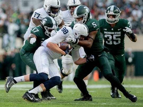 Michigan State's Andrew Dowell, right, tackles Penn
