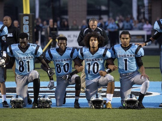 From left, Lansing Catholic football players Kabbash Richards, Roje Williams, Michael Lynn III and Matthew Abdullah knelt during the national anthem before the start of several games during the Cougars' 2017 football season. Lynn and Abdullah, both seniors, no longer attend the school.
