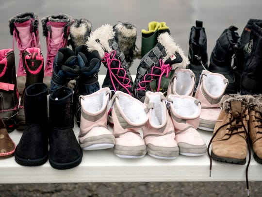 Boots to those in need are displayed on a table outside
