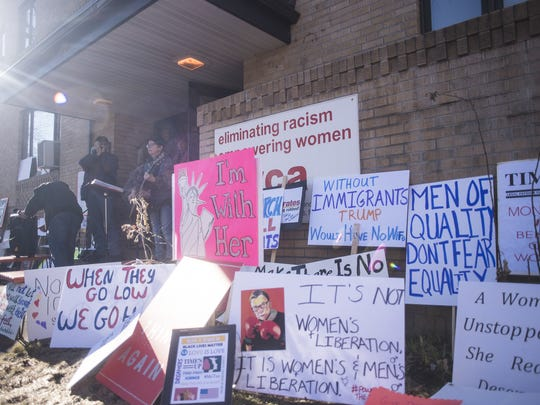 Protestors place their signs outside the YWCA as speakers