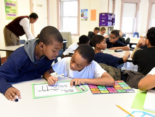 Fourth-grade students Mekhi Walker, 9, left, and Elijah Warren 9,  work together solving a math problem during a math intervention class taught by Paterson Leadership Academy for Young Men.