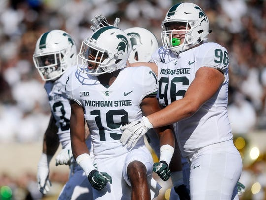 Michigan State's Josh Butler, left, celebrates his