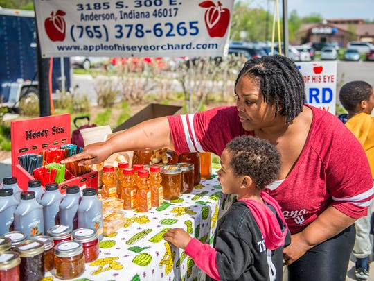 A young customer gets help picking out a honey stick from Apple Of His Eye Orcahrd at the Noblesville Farmers Market at Federal Hill Commons on Saturday, May 5, 2018.