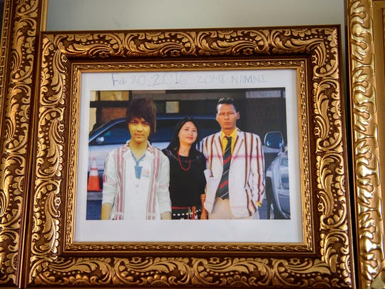 A picture of father Kam Sian Tung, right, and mother Man No and their son Tung Sian Hau, left, whose image was digitally added, hangs on a wall in their home on Wednesday, May 16, 2018, in Lansing.