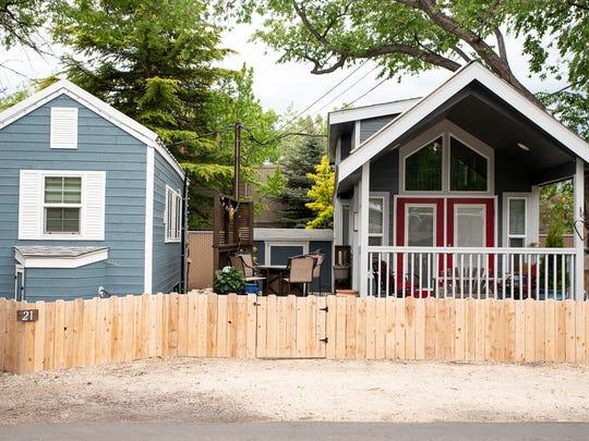 Two tiny-house style trailers sit side by side at the River West Resort RV and trailer park. The two houses are less than 300 square feet and can be hitched to a vehicle and driven away.