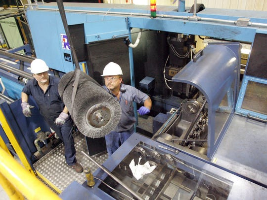 Workers lower a steel brush into a high speed cutting