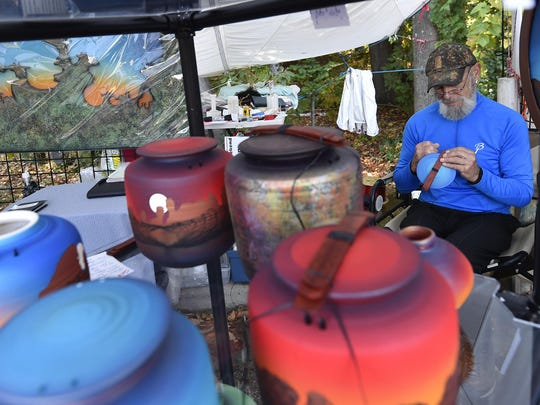 TJ Krueger of Krueger Summer Studio Gallery, Traverse City, Mich., ties ceremonial latches onto the urns he's painted at the juried arts and crafts fair at last year's Sister Bay Fall Fest.