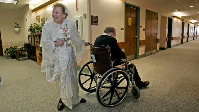 In this image from 2006, Ila Mae Hora pushes her husband Bob through the hall of the Lutheran Home in Wauwatosa, greeting staff and wearing the wedding dress she first wore 60 years earlier.