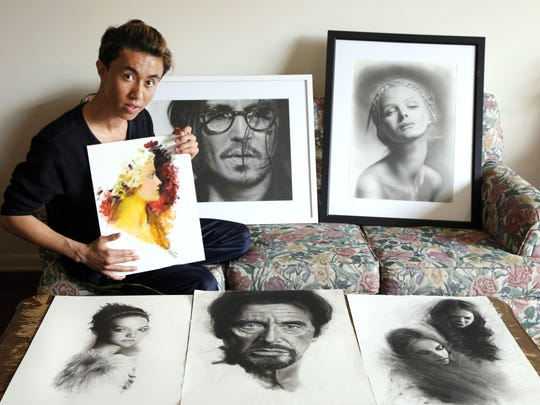 Razmin Ahmadzadah, a 19-year-old artist who was born in Afghanistan and came to Lansing as a refugee, poses with his artworks in a photograph taken for the Refuge Lansing project.
