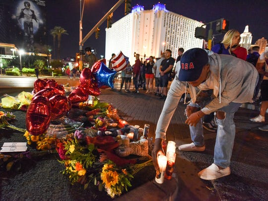 A man places a candle at a makeshift memorial near the Mandalay Hotel on the Las Vegas Strip, in Las Vegas on Oct. 3, 2017, after a gunman killed 58 people and wounded more than 500 others, before taking his own life, when he opened fire from a hotel on a country music festival.