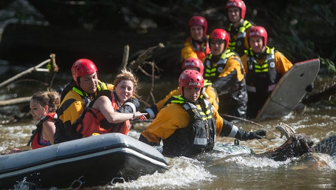 Two females are loaded into a boat by Poudre Fire Authority personnel during a water rescue on the Cache la Poudre River west of College Avenue Friday in Fort Collins. Four tubers were rescued after becoming stranded in the middle of the fast-moving current.