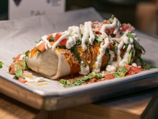 A wet burrito is seen on display on Friday, March 23, 2018, during the Detroit Tigers concessions sneak peek at Comerica Park in Detroit. The burrito includes spanish-style rice, corn and black bean salsa and shredded cheese wrapped in a flour tortilla. It is topped with enchilada sauce, lettuce, pico de gallo, jalape–os and shredded cheese. Served with a side of sour cream and salsa.
