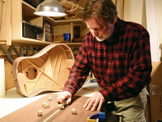 In this March 20, 2018 photo, Luthier Tim Yoder planes