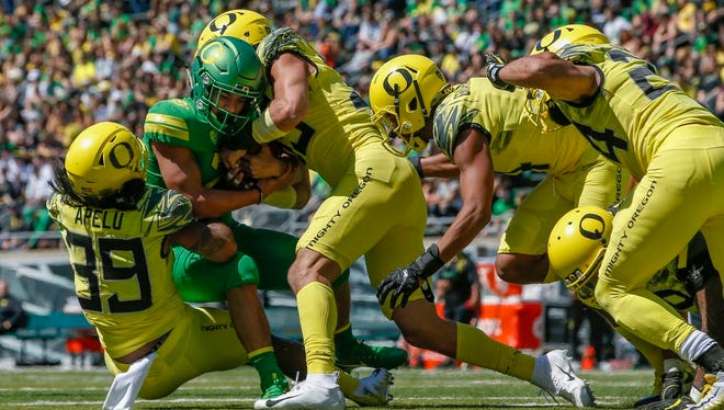 Running back Travis Dye is stopped by Kaulana Apelu, Troy Dye, Thomas Graham Jr. and Keith Simms during the Oregon spring college football game Saturday, April 21, 2018, in Eugene, Ore. (Andy Nelson/The Register-Guard via AP)