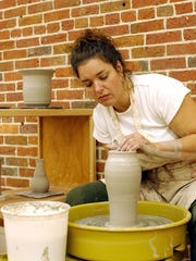 An artist works a potter's wheel at the Clay College, part of Cumberland County Community College, located in the Glasstown Arts District.