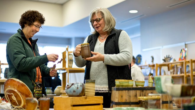 Lisa Bondy and Barb Hill, both of St. Clair, look over pieces by potter Juliet Faber during the 13th annual Potters Market Saturday, November 14, 2015 at the M-TEC building on the SC4 campus in Port Huron.