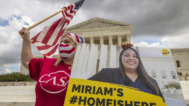 Ivania Castillo from Prince William County, Va., right, holds a banner to show her support for dreamer Miriam from California, as she joins Deferred Action for Childhood Arrivals recipients celebrate in front of the U.S. Supreme Court after the Supreme Court rejected President Donald Trump's bid to end legal protections for young immigrants Thursday in Washington.