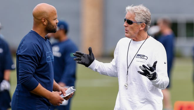 Seattle Seahawks head coach Pete Carroll, right, talks with defensive coordinator Kris Richard, left, during NFL football minicamp in Renton, Wash. Under the watchful eye of Carroll, the Seahawks defense has developed into the best in the NFL.
