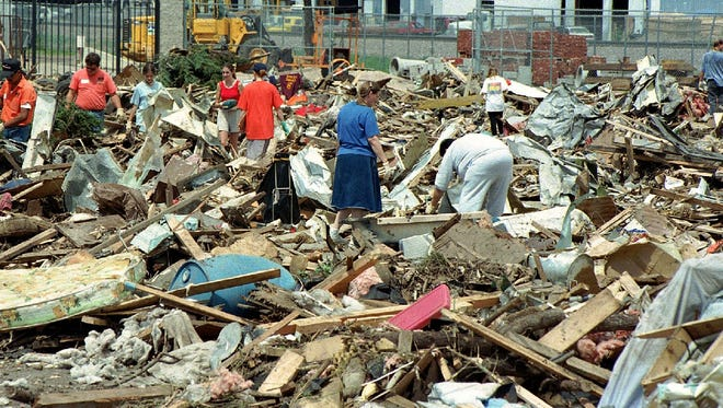 Residents and Fort Collins city workers sort through the rubble a of mobile homes at the Fort Collins Streets Facility Thursday July 31, 1997.