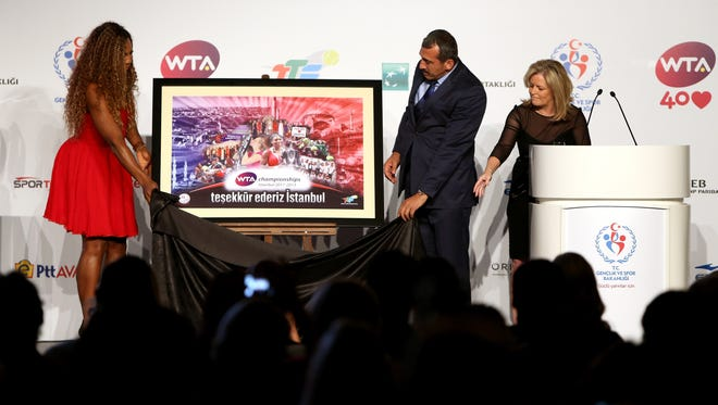Serena Williams and WTA CEO Stacey Allaster present Turkish Tennis Federation President Osman Tural a gift during the draw ceremony for the WTA Championships.
