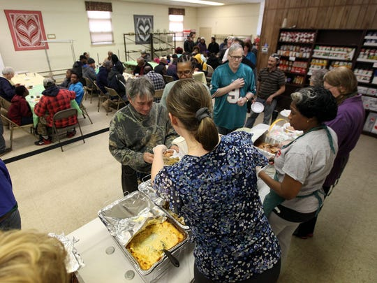 Volunteer Hollie Butler, 25, of Bridgeton (front) pours gravy for Mike Pessolano of Gouldtown during an Easter meal at Bethany Grace Community Church in Bridgeton.