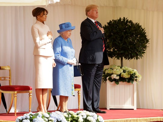 President Trump and first lady Melania Trump stand with Queen Elizabeth II on the dais in the Quadrangle of Windsor Castle Friday.
