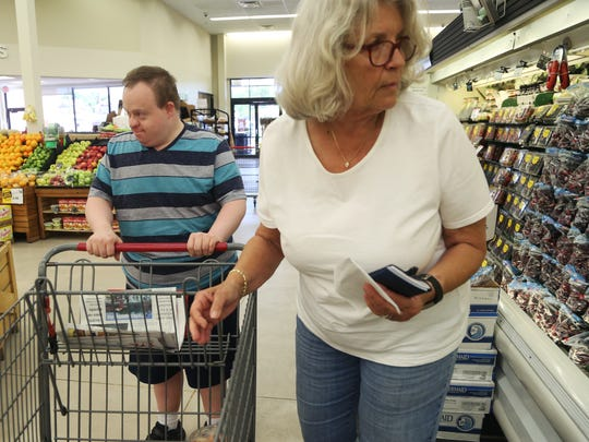 Marty Matteson, of Webster City picks out produce with the help of his staff, Rolanda Burgin, at Hy-Vee on Tuesday, June 6, 2017, in Webster City. Matteson, who has down syndrome, does tasks like cooking and shopping for groceries with the assistance of a staff.
