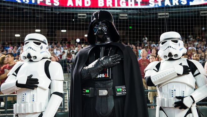 Storm troopers and Darth Vader from Star Wars stand for the national anthem during Star Wars Night during an Arizona Diamondbacks game at Chase Field in Phoenix on Saturday, July 18, 2015.