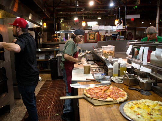 Jeremy Collins, left, Miguel Zamarron and Zack Padilla work in the kitchen Friday at the Three Rivers Pizzeria in Farmington.