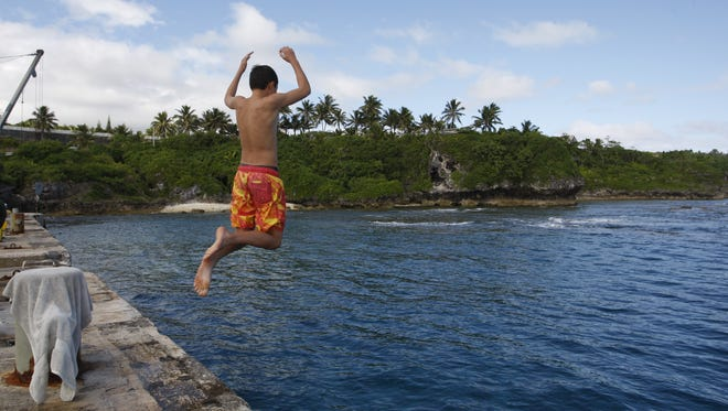 A boy jumps from a wharf in Alofi, Niue. Severe population decline on the tiny Pacific atoll is threatening a culture that dates back more than 1,000 years.