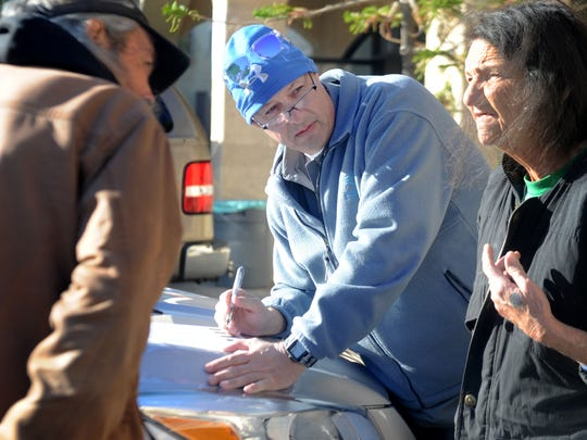 Steven Karnazes, center, interviews James Alexander and Karen Alexander during the Ventura County Homeless Count in Ventura. Volunteers spread out across the county Tuesday in an attempt to survey all homeless residents.