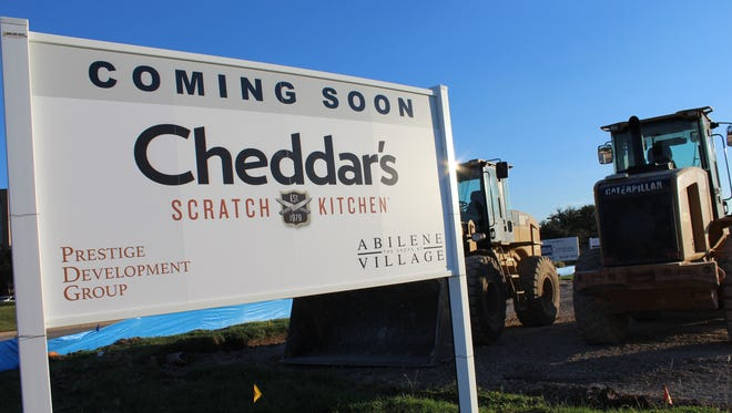 A sign placed near heavy construction equipment announces a Cheddar's Scratch Kitchen will be built at The Shops at Abilene Village in southwest Abilene.