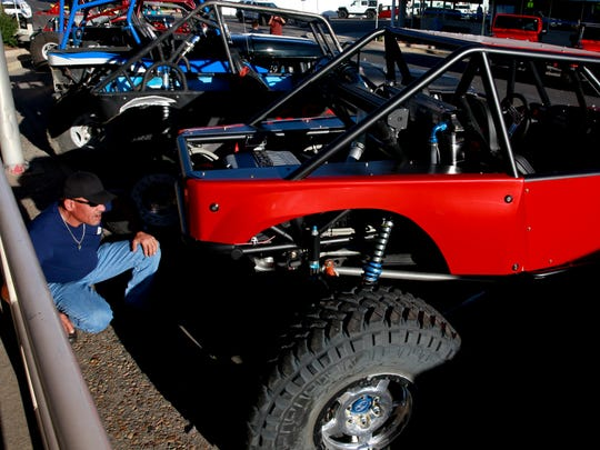 Gene Starks, of Durango, Colo., looks over a rock crawler during a recent Fall Crawl on Main Street in downtown Farmington.