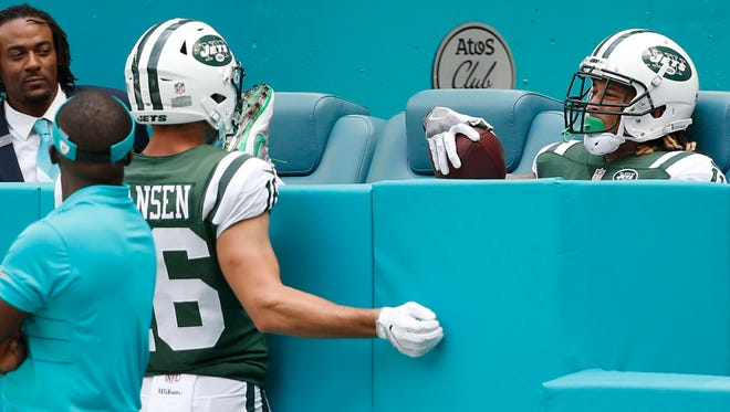 New York Jets wide receiver Chad Hansen (16) watches wide receiver Robby Anderson (11) sitting on the bleachers after scoring a touchdown, during the first half of an NFL football game against the Miami Dolphins, Sunday, Oct. 22, 2017, in Miami Gardens, Fla. (AP Photo/Wilfredo Lee)